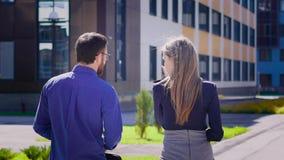 Opinião traseira o homem de negócios e a mulher de negócios que andam junto Homem considerável na camisa que toma uma caminhada a vídeos de arquivo