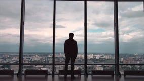 Opinião traseira o homem de negócios em um escritório com opinião panorâmico da cidade O homem de negócios admira a cidade de Win filme