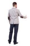 A opinião traseira o homem de negócios no revestimento alcança para fora para agitar as mãos imagem de stock