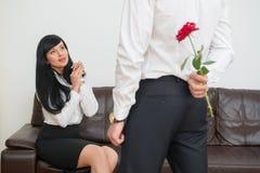 Opinião traseira o homem de negócios novo que esconde uma flor Foto de Stock Royalty Free