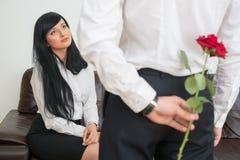 Opinião traseira o homem de negócios novo que esconde uma flor Fotos de Stock Royalty Free