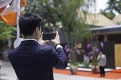 Opinião traseira o homem de negócios novo Taking Photos no evento w do ar livre fotografia de stock