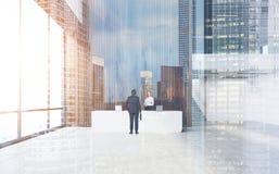 Opinião traseira o homem de negócios perto de uma mesa, opinião da cidade Imagens de Stock Royalty Free