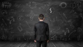 Opinião traseira o homem de negócios que olha a parede preta com esboços desenhados à mão do negócio Fotografia de Stock