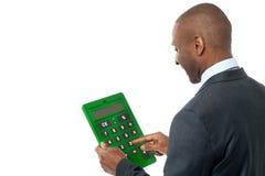 Opinião traseira o homem de negócios que usa a calculadora Fotografia de Stock Royalty Free