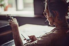 Opinião traseira o homem do freelancer que usa auriculares handsfree para o conversa Imagens de Stock