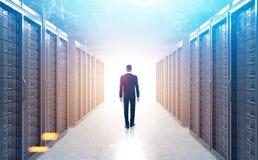 Opinião traseira o homem em uma sala do servidor, luz solar Foto de Stock Royalty Free