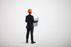 Opinião traseira o homem ereto no vestuário formal e em um capacete de segurança imagem de stock