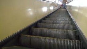 A opinião traseira o homem está escalando uma escada rolante no metro filme