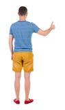 A opinião traseira o homem na camisa quadriculado mostra os polegares acima Fotos de Stock
