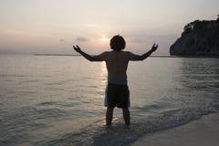 Opinião traseira o homem novo com os braços estendido na praia no por do sol fotografia de stock royalty free
