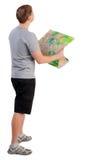 Opinião traseira o homem novo da viagem que olha o mapa Imagem de Stock