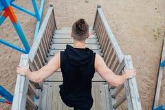 A opinião traseira o homem novo do esporte com vitelas fortes muscle o levantamento fora no campo de jogos imagem de stock royalty free