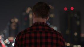 Opinião traseira o homem novo do moderno que olha a vista da cidade na noite filme