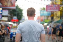 Opinião traseira o homem novo do turista contra a vista da estrada de Khao San em Banguecoque imagem de stock