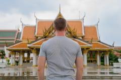 Opinião traseira o homem novo do turista contra a vista do templo budista em Banguecoque fotos de stock royalty free