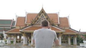 Opinião traseira o homem novo do turista que fotografa a vista do templo budista em Banguecoque filme
