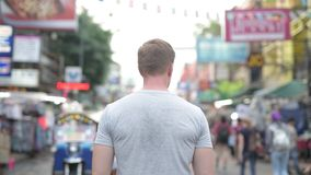 Opinião traseira o homem novo do turista que olha em torno da estrada de Khao San em Banguecoque vídeos de arquivo