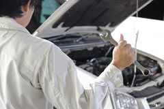 Opinião traseira o homem novo profissional do mecânico na chave guardando uniforme contra o carro na capa aberta na garagem do re Imagem de Stock
