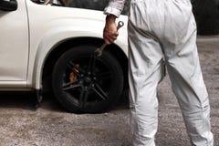 Opinião traseira o homem novo profissional do mecânico na chave guardando uniforme contra o carro na capa aberta na garagem do re Foto de Stock