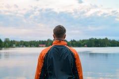 Opinião traseira o homem novo que aprecia a vista do lago fotos de stock