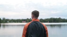 Opinião traseira o homem novo que aprecia a vista do lago filme