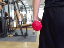 Opinião traseira o homem novo saudável que guarda o peso no gym do esporte Conceito da aptidão e do exercício imagem de stock royalty free