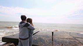 A opinião traseira o homem que abraça a mulher e que aprecia o mar video estoque