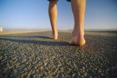 Opinião traseira o homem que anda ao longo da estrada Imagem de Stock Royalty Free