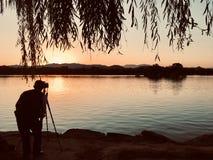 Opinião traseira o homem que está fotografando o por do sol imagens de stock
