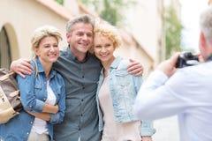 Opinião traseira o homem que fotografa os amigos masculinos e fêmeas na cidade Foto de Stock Royalty Free