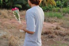 A opinião traseira o homem relaxado novo está guardando um ramalhete bonito de rosas vermelhas no fundo borrado natureza Amor e r Foto de Stock Royalty Free