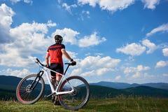 Opinião traseira o motociclista profissional atlético novo do turista que está na bicicleta sobre o monte fotografia de stock