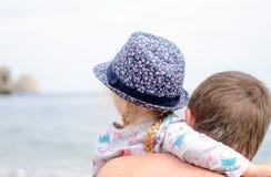 Opinião traseira o pai e a filha que olham a água Imagens de Stock