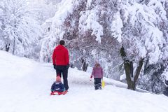 A opinião traseira o pai que sledding seu bebê pequeno e uma outra filha andam com eles, parque de Segmenler, Ancara imagens de stock