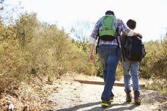 Opinião traseira o pai And Son Hiking no campo imagem de stock