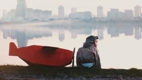 Opinião traseira o rapaz pequeno no traje piloto velho que senta-se perto de lago surpreendente da cidade com do avião vermelho d video estoque