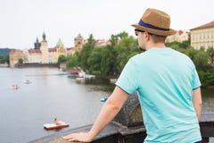 Opinião traseira o turista à moda feliz em Charles Bridge, Praga, República Checa Homem considerável que viaja em Europa fotos de stock
