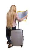 Opinião traseira o viajante da mulher que senta-se em suas malas de viagem e que procura um mapa de rota Fotografia de Stock Royalty Free