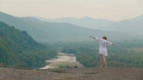A opinião traseira o viajante louro bonito com mãos levantadas que anda lentamente ao longo da borda das montanhas zangão video estoque