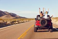 Opinião traseira os amigos na viagem por estrada que conduz no carro convertível Fotografia de Stock Royalty Free