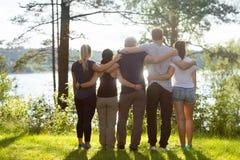 Opinião traseira os colegas de trabalho que estão os braços ao redor na floresta Imagem de Stock