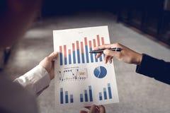 Opinião traseira os colegas que examinam o gráfico dos papéis de negócio imagem de stock royalty free