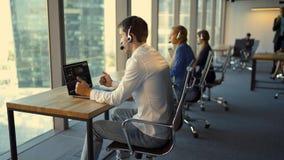 Opinião traseira os empresários nos auriculares usando portáteis ao trabalhar no escritório filme