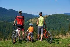 Opinião traseira os motociclistas, a mamã, o paizinho novo e a criança modernos da família do turista estando com bicicletas fotos de stock