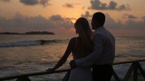 Opinião traseira os noivos que aprecia o por do sol na praia tropical perto da balaustrada em férias Recém-casados que abraçam e filme