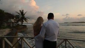 Opinião traseira os noivos que aprecia o por do sol na praia tropical perto da balaustrada em férias Recém-casados que abraçam e video estoque