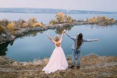 A opinião traseira recém-casados à moda dos pares com mãos acima está levantando antes de um lago no monte Cerimônia de casamento Imagem de Stock
