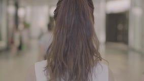 Opinião traseira reta indo da mulher moreno do cabelo filme