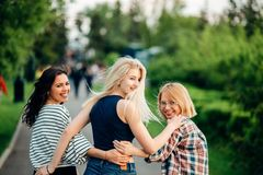 Opinião traseira três mulheres bonitas que sentam-se na grama e nos abraços Foto de Stock Royalty Free